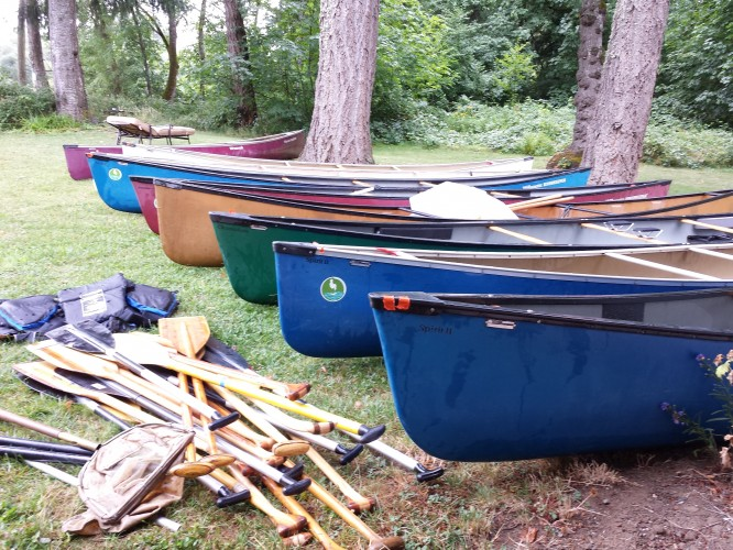 Canoes in a row, at Willamette River haul-out, Day 3 Watershed Down Camp.