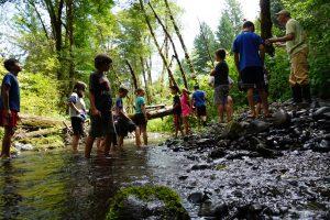 Kids standing in stream.